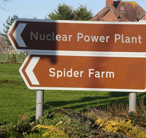 "Two signs pointing same direction: ""Nuclear Power Plant"" and ""Spider Farm"""